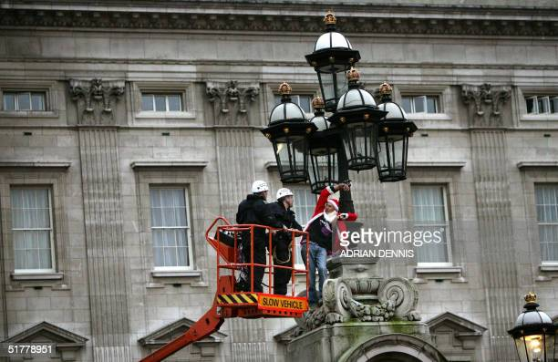 Police officers approach Robert Pyke dressed as Santa Claus, a Fathers for Justice campaigner, who chained himself atop the gate post of Buckingham...