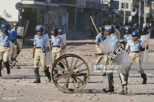 Police officers are pelted with stones during an antigovernment general strike in Dhaka Bangladesh circa 1989