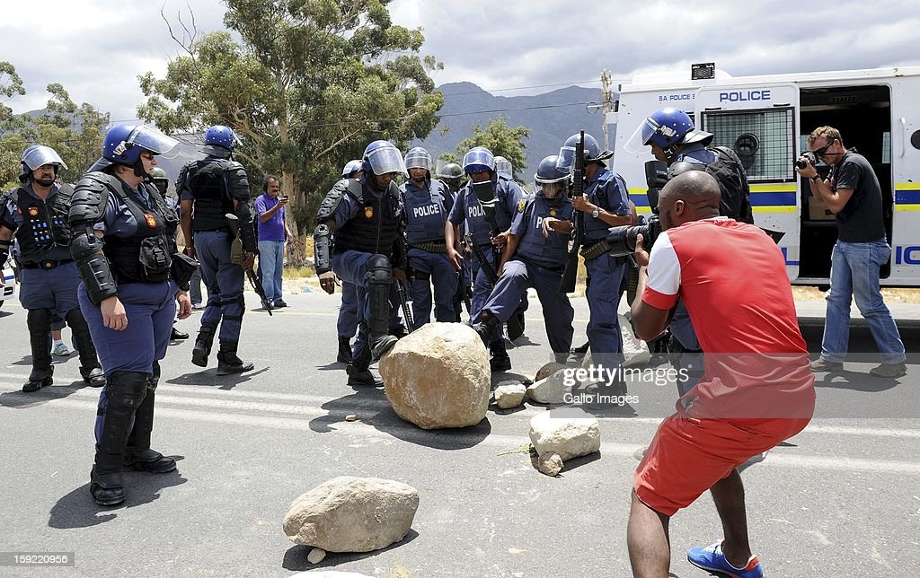 Police officers are photographed at the N1 De Doorns protest on January 9, 2013, in Cape Town, South Africa. The farm workers shut down the N1 by lighting tires on fire and placing large rocks on the road.