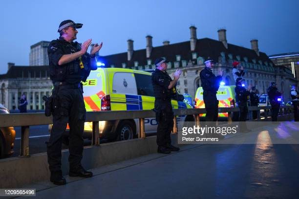 Police officers are seen applauding NHS staff and key workers on Westminster Bridge on April 09 2020 in London England Following the success of the...