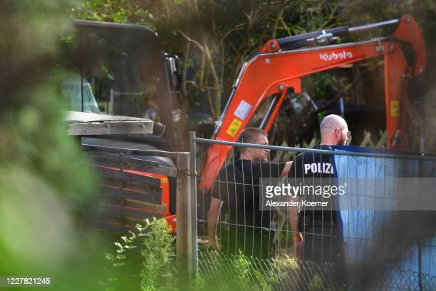 Police officers are seen gesturing behind fencing at an allotment as police continue to search the area in relation to the disappearance of Madeleine...
