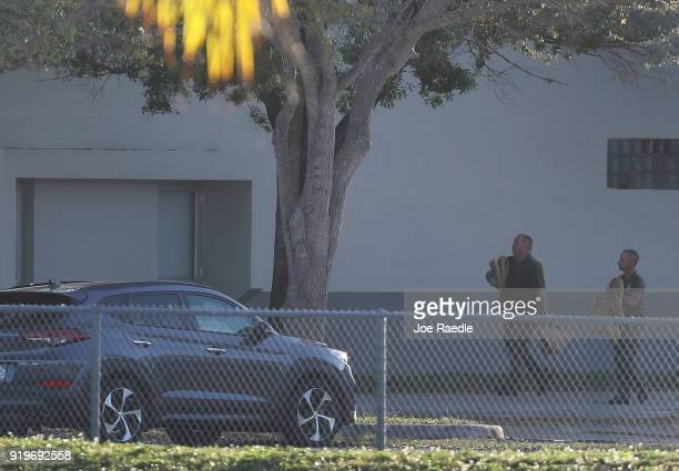 Police officers are seen in front of Marjory Stoneman Douglas High School as law enforcement officials continue their work investigating the 17...