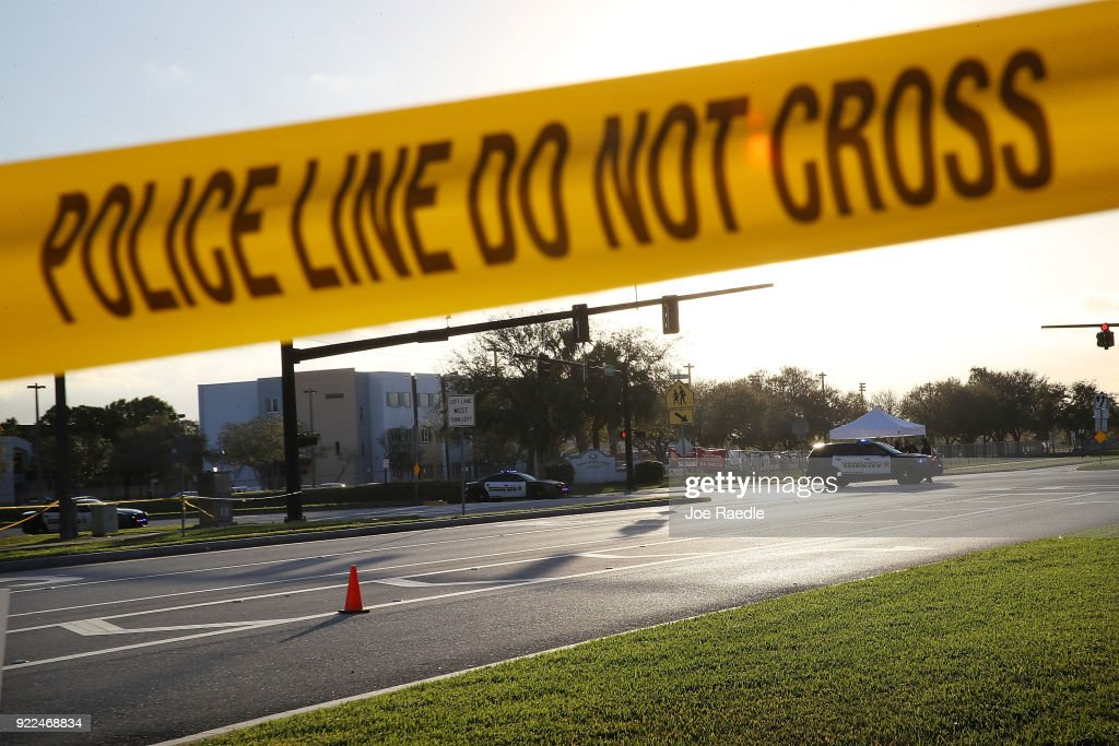 Police officers are seen in front of Marjory Stoneman Douglas High School as law enforcement officials continue their work investigating the 17 people who were killed at the school on February 17, 2018 in Parkland, Florida. Police arrested 19 year old former student Nikolas Cruz in the killing of the high school students.
