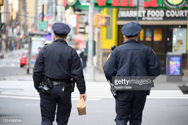 NYPD police officers are seen in Times Square hours ahead of the implementation of 'New York State on PAUSE' executive order as the coronavirus...