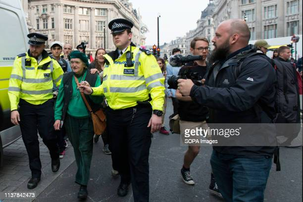 Police officers are seen leading away an activist in Oxford Circus during the Extinction Rebellion Strike in London Environmental activists from...