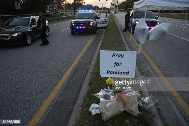 Police officers are seen near Marjory Stoneman Douglas High School as law enforcement officials continue their work investigating the 17 people who...