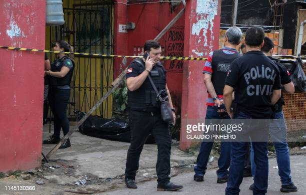 Police officers are seen outside a bar after a shooting in Belem Para state Brazil on May 19 2019 At least 11 people were shot dead Sunday at a bar...