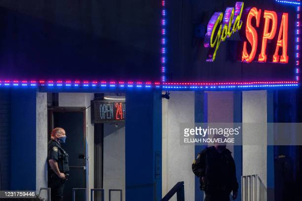 Police officers are seen outside a massage parlor where three people were shot and killed on March 16 in Atlanta, Georgia. - Eight people were killed...