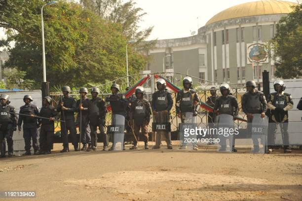 Police officers are seen outside Monrovia's Capitol building while members of the Council of Patriots protest against the deepening economic crisis...