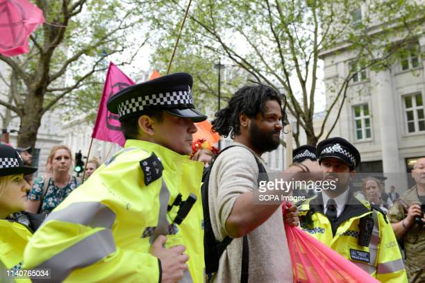 Police officers are seen removing an Extinction Rebellion environmental activists that was blocking the street outside the Embassy of Brazil in...