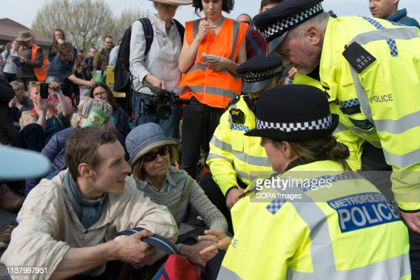 Police officers are seen speaking with an activist during the Extinction Rebellion Strike in London Environmental activists from the Extinction...