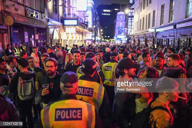 Police officers are seen walking through heavy crowds in Soho on July 4, 2020 in London, United Kingdom. The UK Government announced that Pubs,...