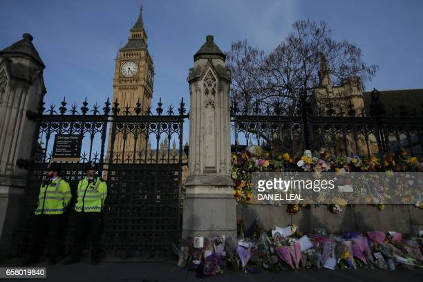 TOPSHOT Police officers are seen with floral tributes to the victims of the March 22 terror attack in front of the Elizabeth Tower more commonly...