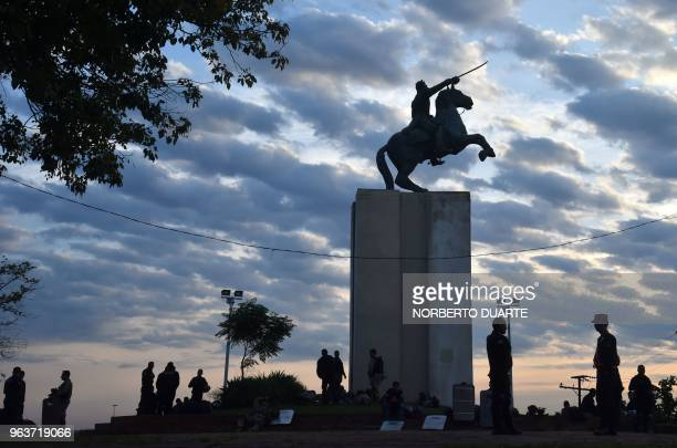 Police officers are silhouetted against a cloudy sky as they stand guard at a square in the surroundings of the Congress in Asuncion on May 30 after...