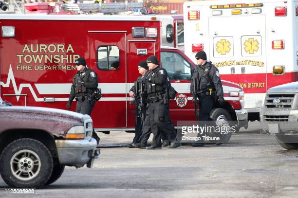 Police officers armed with rifles stage near a commercial building where an active shooter was reported in the 600 block of Archer Avenue in Aurora...