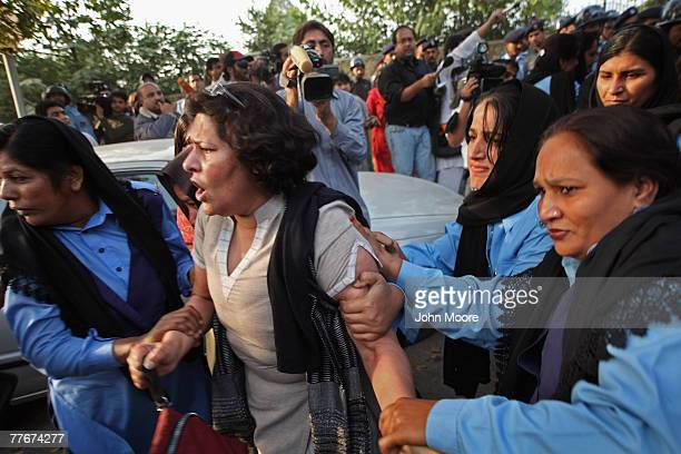 Police officers arrest a civil rights activist at an antigovernment protest on November 4 2007 in Islamabad Pakistan A small group of protesters held...