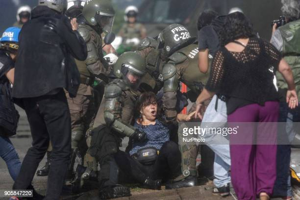 Police officers arrest a demonstrator during a demonstration against Pope Francisco's visit to Chile in the vicinity of Parque O'Higgins in...