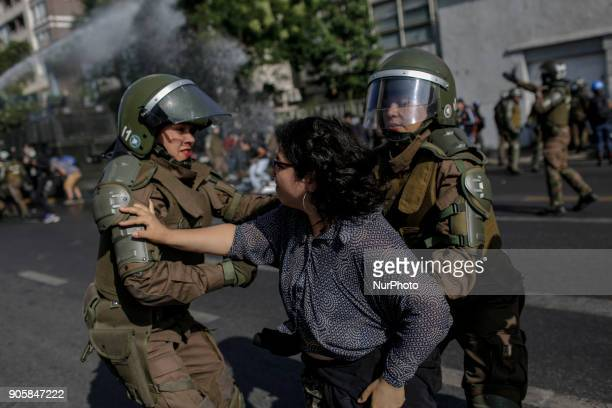 Police officers arrest a demonstrator during a demonstration against Pope Francisco's visit to Chile in the vicinity of Parque O'Higgins in Santiago...