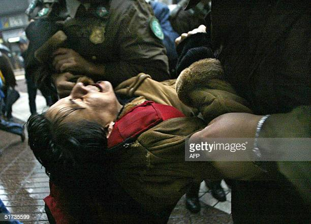 Police officers arrest a demonstrator during a protest against the Asia-Pacific Economic Cooperation forum in Santiago, 12 November 2004. Top leaders...