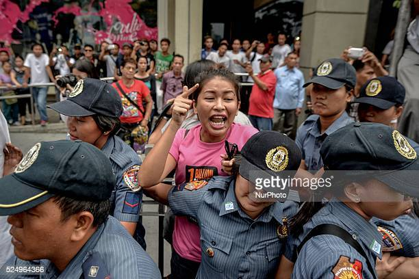 Police officers arrest a demonstrator during a protest near the venue of the World Economic Forum on East Asia at the financial district of Makati...