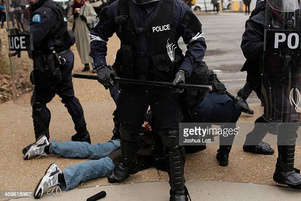 Police officers arrest a demonstrator protesting the shooting death of Michael Brown at City Hall November 26 2014 in St Louis Missouri Brown a...
