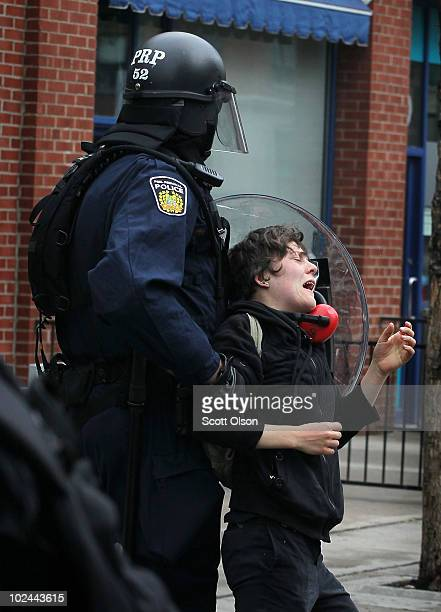 Police officers arrest a demonstrator who was protesting the G8/G20 summits on June 26, 2010 in Toronto, Ontario Canada. Store windows were smashed...
