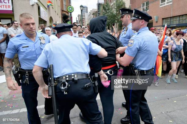 Police officers arrest a female later identified as Ryan Segin after she attempted to lit a Blue Lives Matter flag in protest ahead of the Pride...