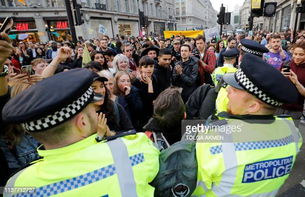 Police officers arrest a man at a camp set up by climate change activists at Oxford Circus on the third day of its blockade by environmental protest...