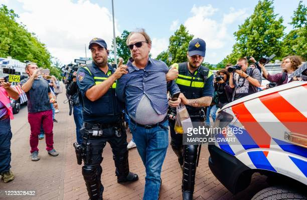 Police officers arrest a man taking part in a prohibited demonstration against the government's measures taken to stop the spread of the Covid-19...