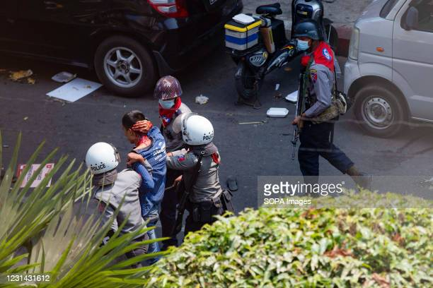 Police officers arrest a protester cover in blood during a demonstration against the military coup. Myanmar police fire rubber bullets, real bullets,...