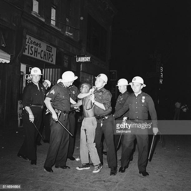 Police officers arrest a protester who was shot in the leg during riots in Harlem sparked by the killing of a 15 year old boy by police.