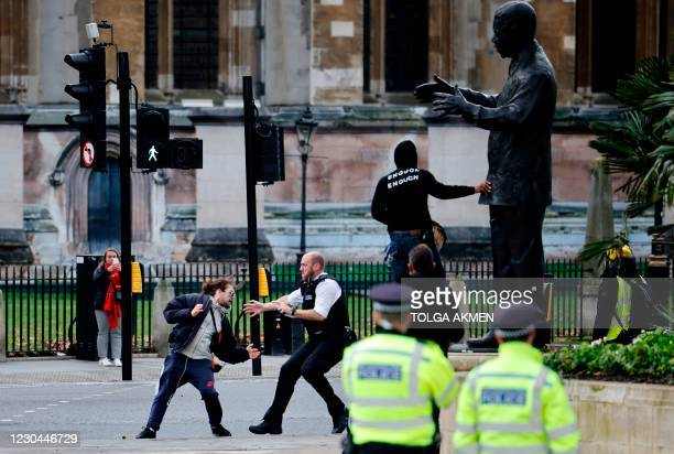 Police officers arrest a protestor during an anti-COVID-19 lockdown demonstration outside the Houses of Parliament in Westminster, central London on...