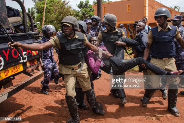TOPSHOT Police officers arrest a supporter of Ugandan musician turned politician Robert Kyagulanyi commonly known as Bobi Wine before his arrest on...