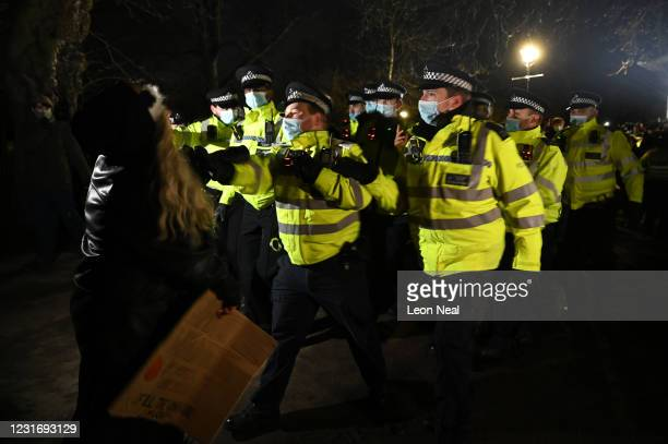 Police Officers arrest a woman during a vigil on Clapham Common, where floral tributes have been placed for Sarah Everard on March 13, 2021 in...