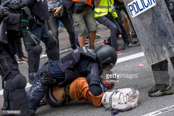 Police officers arrest a young protester during a demonstration called by students on October 18 on the day that separatists have called a general...