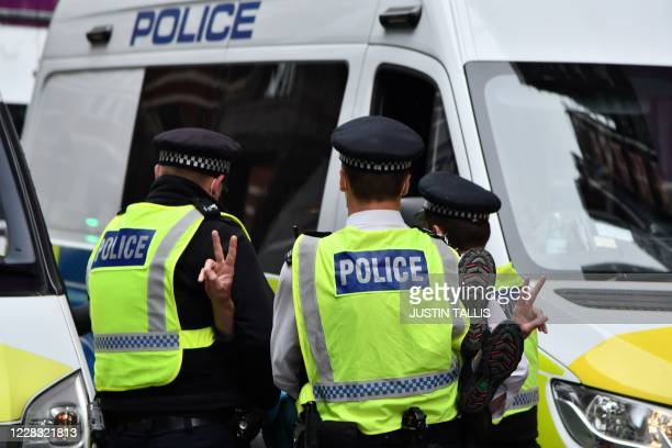 Police officers arrest an activist from the climate protest group Extinction Rebellion who was blocking the road protesting against animal farming...