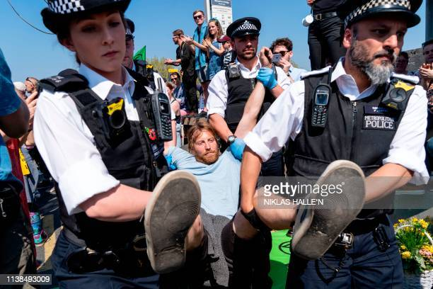Police officers arrest and carry away a climate change activist from a demonstration blocking Waterloo Bridge in London on April 21 on the seventh...