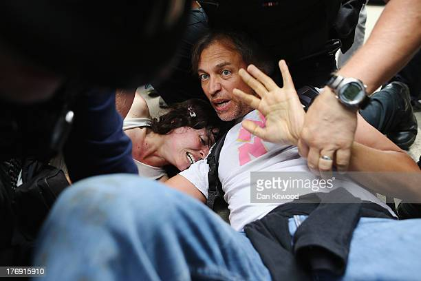 Police officers arrest protesters outside a drill site operated by Cuadrilla Resources Ltd on August 19 2013 in Balcombe West Sussex Protesters...