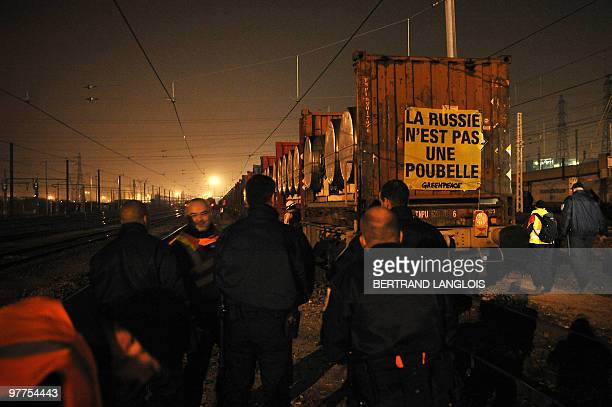 Police officers arrive as Greenpeace environmental activists put a banner reading 'Russia is not a trash' onto a train loaded with depleted uranium...