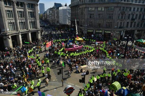 Police officers arrive at Oxford Circus as they prepare to remove protesters during the fifth day of a coordinated protest by the Extinction...