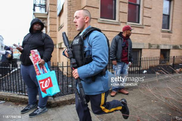 Police officers arrive at the scene of an active shooter in Jersey City New Jersey on December 10 2019 One officer was shot when two gunmen with a...