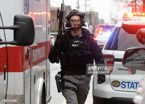 Police officers arrive to the scene where active shooting is happening in Jersey City on December 10, 2019. - One officer was shot when two gunmen...