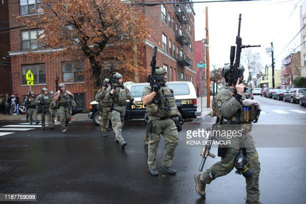Police officers arrive to the scene where an active shooting was taking place in Jersey City New Jersey on December 10 2019 One officer was shot when...