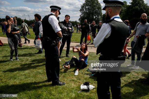 Police officers ask people to go home during a demonstration against the coronavirus lockdown in Hyde Park on May 16, 2020 in London, United Kingdom....