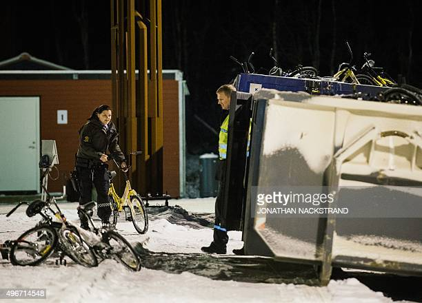 Police officers at the Norwegian border crossing station at Storskog throw bikes used to cross the border from Russia by refugees to a recycle...