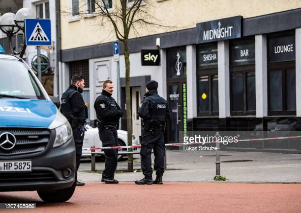Police officers at the scene outside the Midnight hookah bar, one of two bars that were targeted by a gunman last night, on February 20, 2020 in...