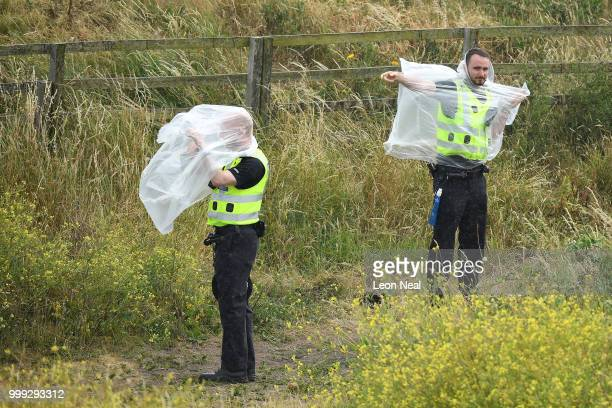 Police officers attempt to don ponchos as US President Donald Trump plays a round of golf at Trump Turnberry Luxury Collection Resortduring the US...