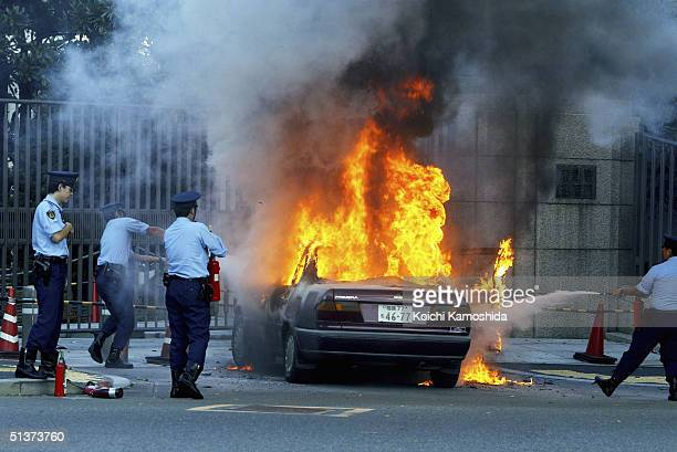 Police officers attempt to extinguish the flames engulfing the burning wreck of a car after it was crashed into a gate at the Parliament building...