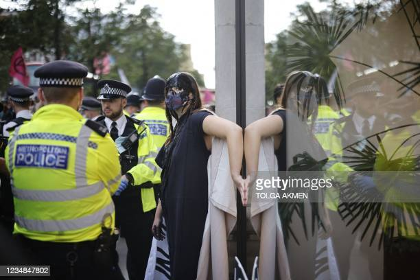 Police officers attend as a climate activist from the Extinction Rebellion group demonstrates with a hand glued to the window of the Selfridges store...