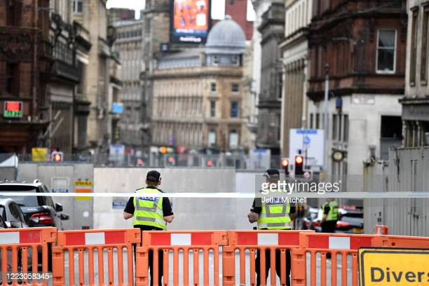 Police officers attend the scene after a man was shot dead after a stabbing in a central Glasgow hotel on June 27, 2020 in Glasgow, Scotland. A...